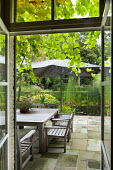 View from inside house, table and chairs on patio under umbrella, pond