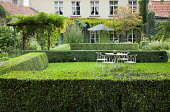 Metal table and chairs on lawn in clipped box hedge enclosure, garden 'room'