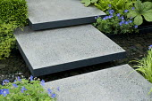 Polished concrete stepping stones across pond