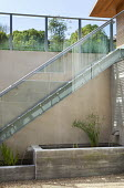 Basement courtyard with concrete raised pond and fountain, Cyperus papyrus, glass and metal staircase