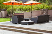 Outdoor rattan chairs, sofas and tables under large umbrella on raised terrace