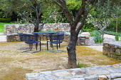 Metal table and chairs in Mediterranean-style olive grove surrounded by dry-stone wall enclosure, sandy terrace