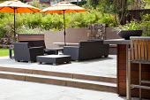 Outdoor rattan chairs, sofas and tables under large umbrellas on raised terrace