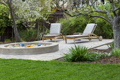 Moveable recliner chairs on wheels on terrace by sandpit