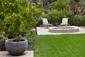 Moveable recliner chairs on wheels on terrace by circular sandpit, orange tree in border