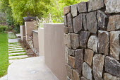Stone and concrete walls at different levels, stepping stone path through lawn