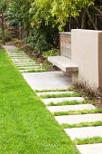 Built-in bench on concrete and timber wall, stepping stone path across lawn