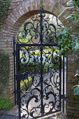Black wrought iron gate under arch in brick wall