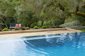 Petanque pitch by swimming pool, bench