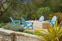 Blue Adirondack chairs around brazier on Mediterranean terrace, phormiums