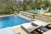 Contemporary recliner chairs with cushions on swimming pool terrace, blue Adirondack chairs around brazier on Mediterranean terrace
