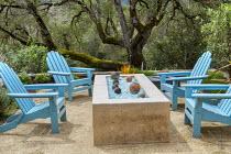 Blue Adirondack chairs around brazier on Mediterranean terrace, Quercus lobata