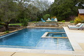 Swimming pool, recliner chairs on terrace, blue Adirondack chairs around brazier on Mediterranean terrace, phormiums