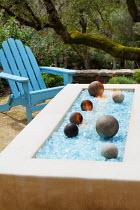 Blue Adirondack chair by brazier on Mediterranean terrace, blue glass
