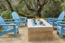 Blue Adirondack chairs around brazier on Mediterranean terrace