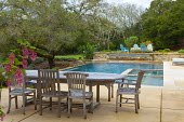 Wooden table and chairs on swimming pool terrace