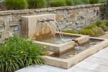Water spout fountain on Mediterranean terrace, stone wall