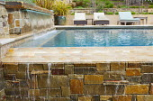 Stone walls, contemporary chairs on swimming pool terrace