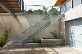 Basement courtyard with concrete raised pond and fountain, rendered wall, Cyperus papyrus, gravel driveway, garage