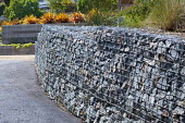 Reclaimed stone gabion wall made from stones recycled from on site demolition, Phormium 'Sunset'