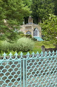 View over oriental-style blue painted metal fence to Orangery, magnolia