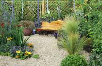 Natural timber bench in gravel garden, Stipa tenuissima, crocosmia