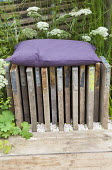 Cushion on stool made from reclaimed scaffolding boards, Alchemilla mollis, Carex grayi
