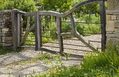 Timber framed gate with metal bars between stone gateposts, driveway
