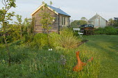 Terracotta ducks in long grass meadow, orchrd, pavilion, white bench, wooden cart, greenhouse