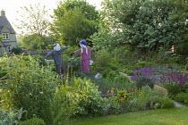 Scarecrows in kitchen garden, Shallot 'Pikant' in raised bed, Symphytum orientale, Geum 'Totally Tangerine'