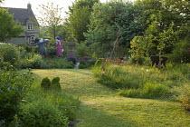 Fruit trees in long grass meadow, scarecrows, terracotta birds ornaments