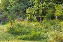 Terracotta duck ornaments in long grass meadow, orchard