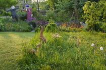 Terracotta duck ornaments in long grass meadow