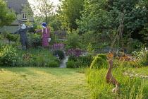 Scarecrows in kitchen garden, Geum 'Totally Tangerine', terracotta duck ornaments in long grass meadow
