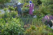 Scarecrows in kitchen garden, Shallot 'Pikant' in raised bed, Geum 'Totally Tangerine'
