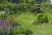 Wooden wheelbarrow in long grass under fruit trees, topiary chicken, Geum 'Totally Tangerine'