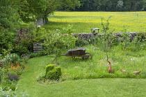 Wild garden, bird ornaments, meadow, wooden wheelbarrow, bird table