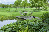 Table and chairs on decking by pond, geranium, Polygonatum x hybridum