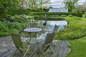 Table and chairs on decking overlooking pond