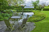 Table and chairs on decking overlooking pond, frog sculpture by Luc Lapere