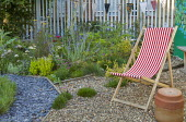 Red striped deckchair on gravel terrace, herb border, sage, thyme, chives, perovskia, artichokes