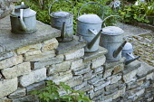Old metal watering cans on stone stepped wall