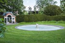 Circular pool in lawn, pavilion