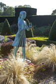 'Girl holding the Lamp of Wisdom' by Nathan David, Stipa tenuissima, hylotelephium syn. sedum, clipped box topiary and yew hedges