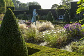 Statue of a girl in herb parterre garden surrounded by rows of box pyramid topiary in low clipped box hedge, aster, Stipa tenuissima, cosmos, view to bench