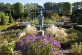 Statue of a girl by Nathan David in formal parterre garden, aster, Stipa tenuissima, pergola