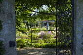 View though ornate metal gate into formal garden, girl statue by Nathan David