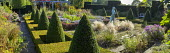 Formal garden, parterre surrounded by rows of clipped box pyramids, girl statue by Nathan David, Stipa tenuissima, view to bench, pergola, berberis, box and yew hedges