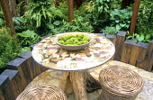Tree trunk table, woven willow stools on patio, timber edging, hostas and ferns, moss in container