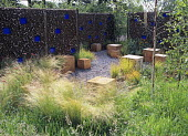 Drifts of grasses in enclosed garden with randomly placed large wooden seats, design by Andy Sturgeon, gabion walls